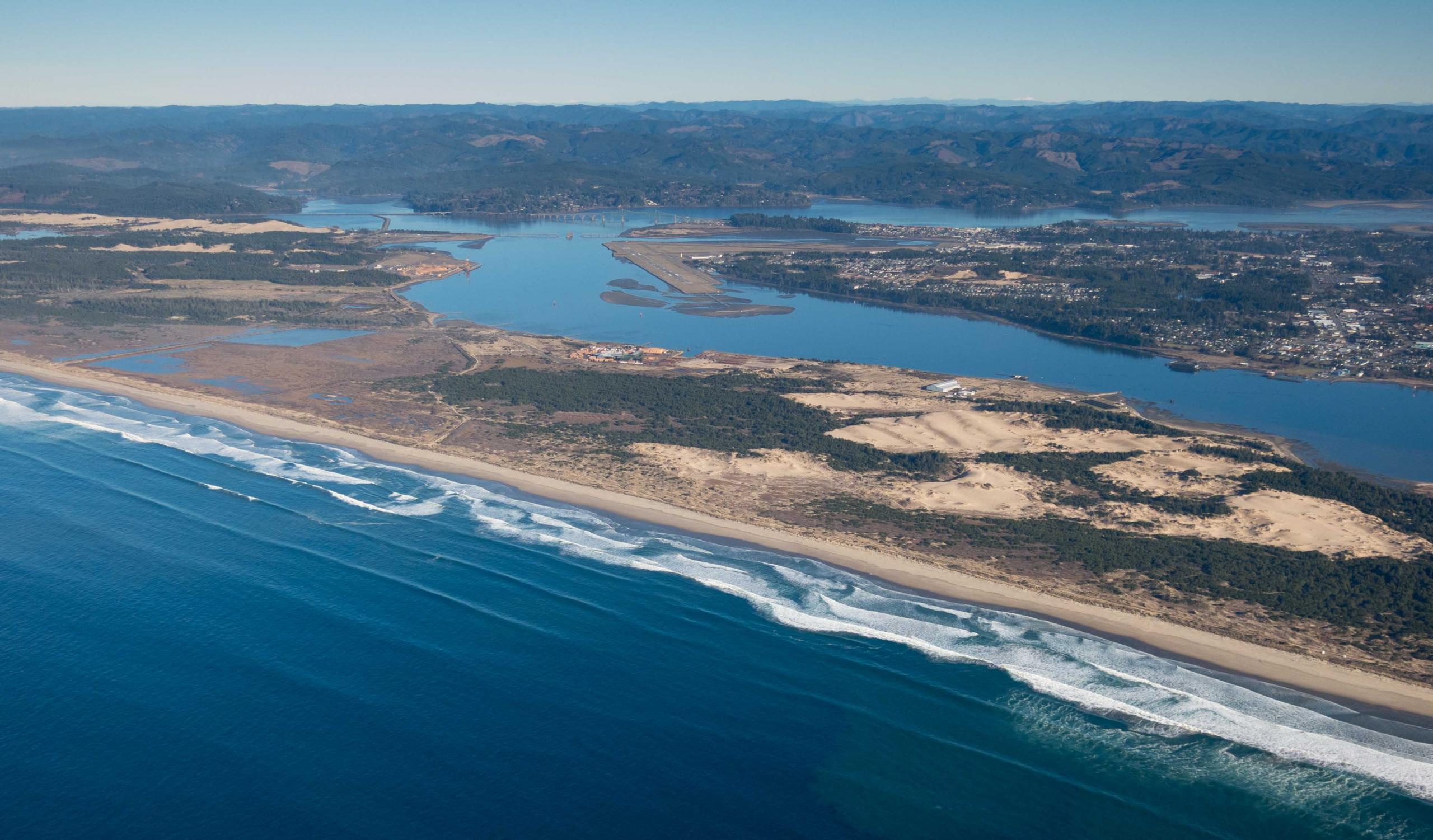 Photo of Coos Bay's North Spit -- note North Bend airport runway in the distance, pointed at where the LNG tanks would have been built, by Alex Derr.