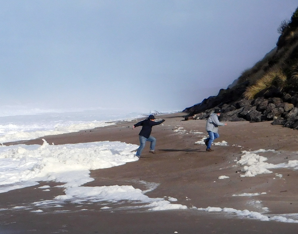 Beachgoers fleeing a rising tide at Gleneden Beach.\Photo by Linda Reid.