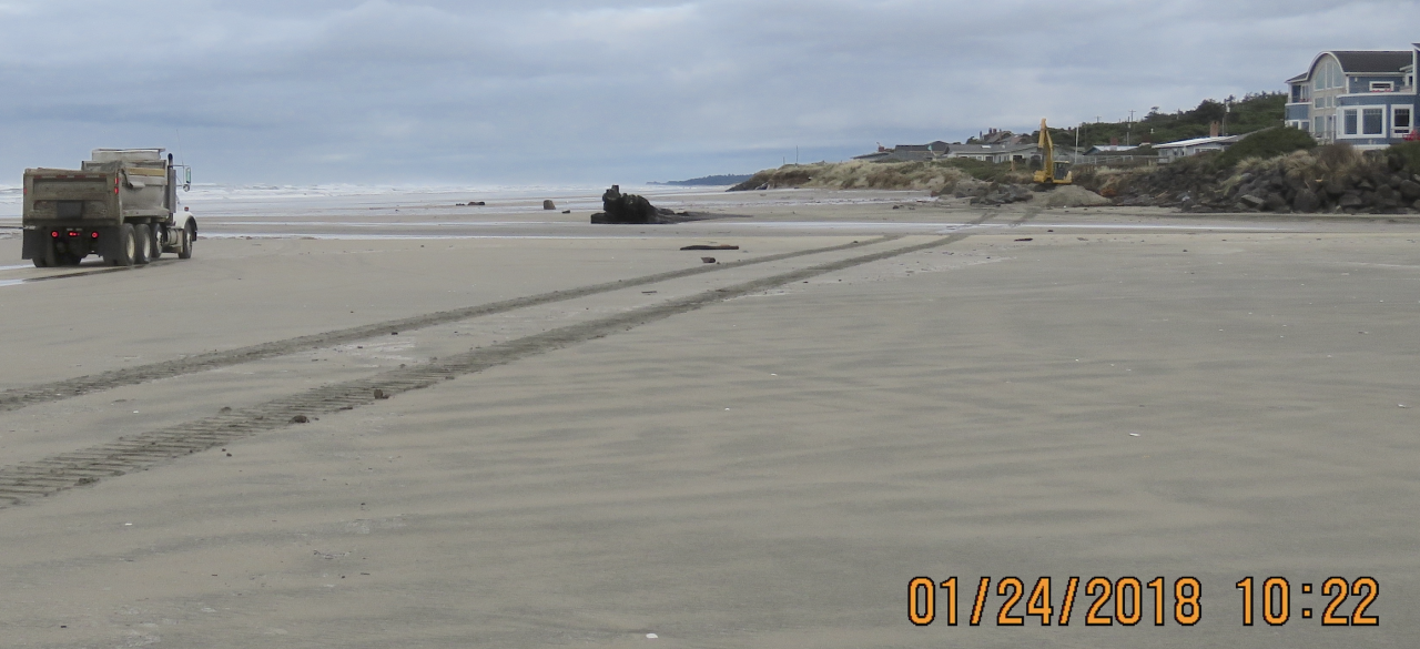 Dump truck on beach, dump truck delivers boulders to to rip-rap site