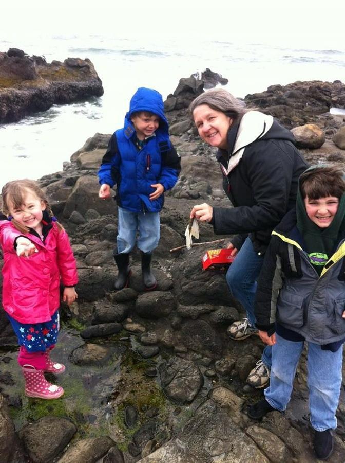 Fawn Custer exploring the rocky shores with kids. Photo courtesy of the Oregon Coast Aquarium.