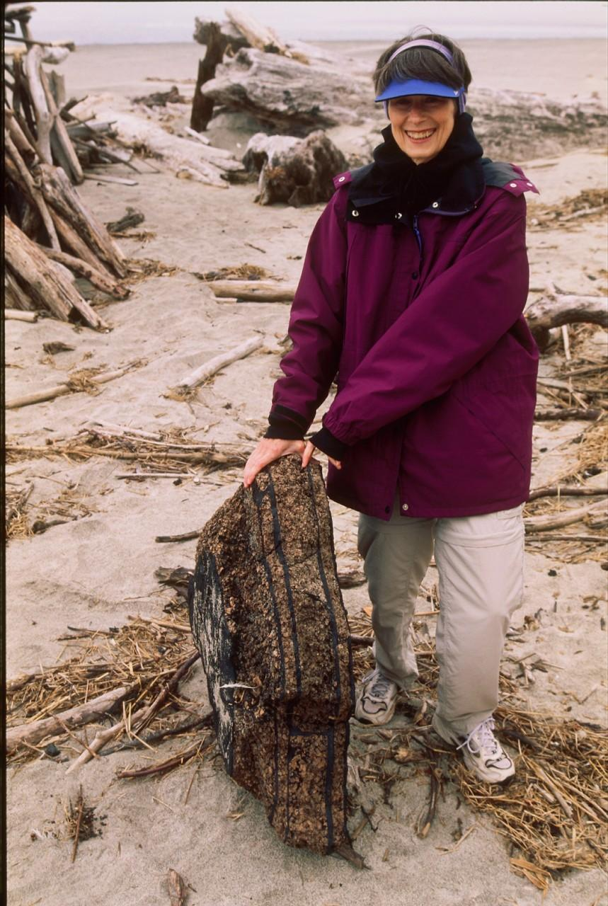 Theda Hastie, holding up what looks like a piece of a walkway or some other human-made surface, made of what looks like cork pieces in a layer, alternating with layers of black tar (the shiny kind). It's pretty heavy to boot, probably not a floater.