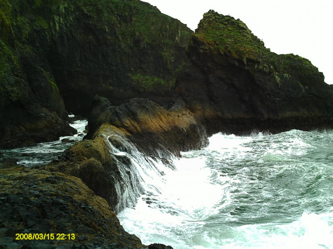 Waves coming in and pounding on this monolith of a rock on a relatively calm day. The Northerly entrance to Sea Lion Caves is on the far left.
