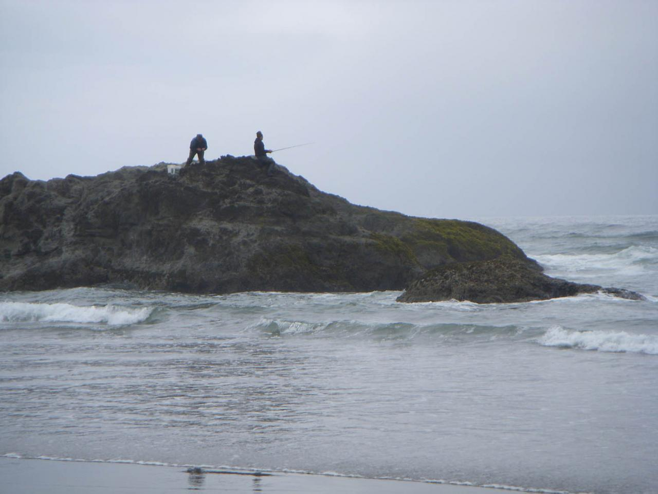 Two men fishing from an offshore rock
