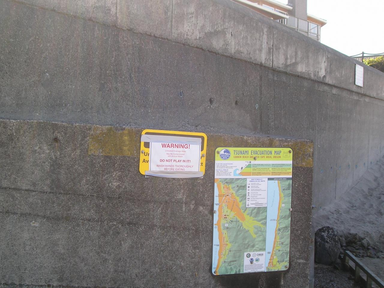sign reads: Warninguntreated drainage watermay be contaminated with animal wastedo not play in itwash hands thoroughly before eating