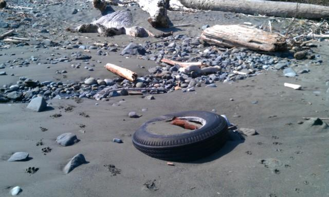 On the beach just Off Seacliff Terrace, Brookings, just north of the North jetty of the Chetco River, there is an old tire stuck in the sand.