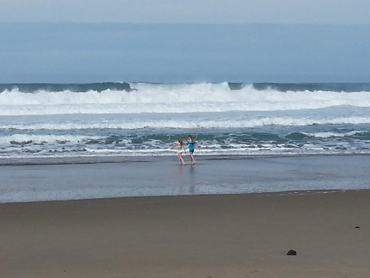 Two young girls playing in the surf.