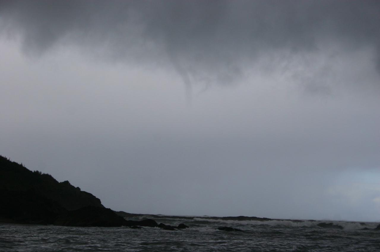 A funnel cloud approaching that possibly was a water spout. Observed some water disturbance though did not see it connect to water.