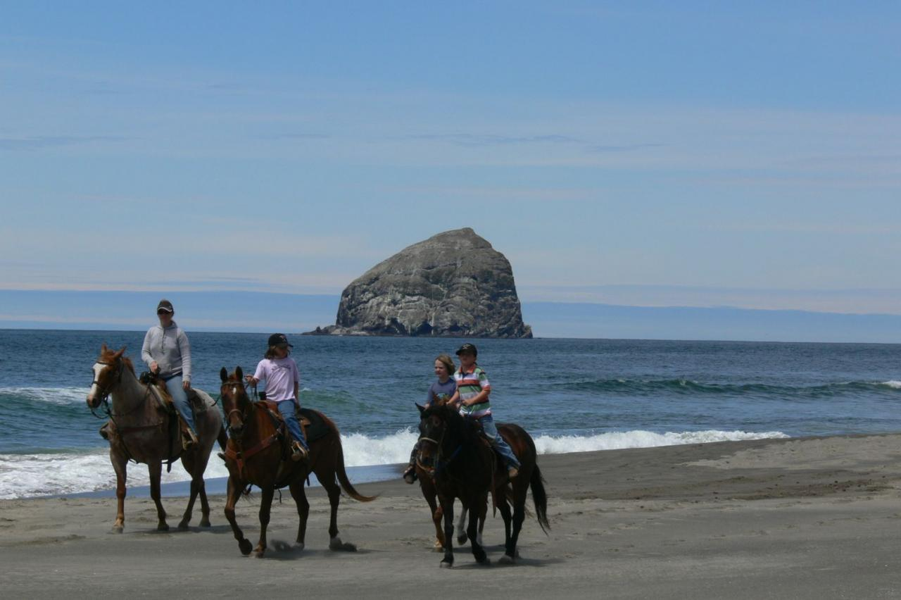 Four riders on the beach at Bob Straub State Park in Pacific City, Oregon.