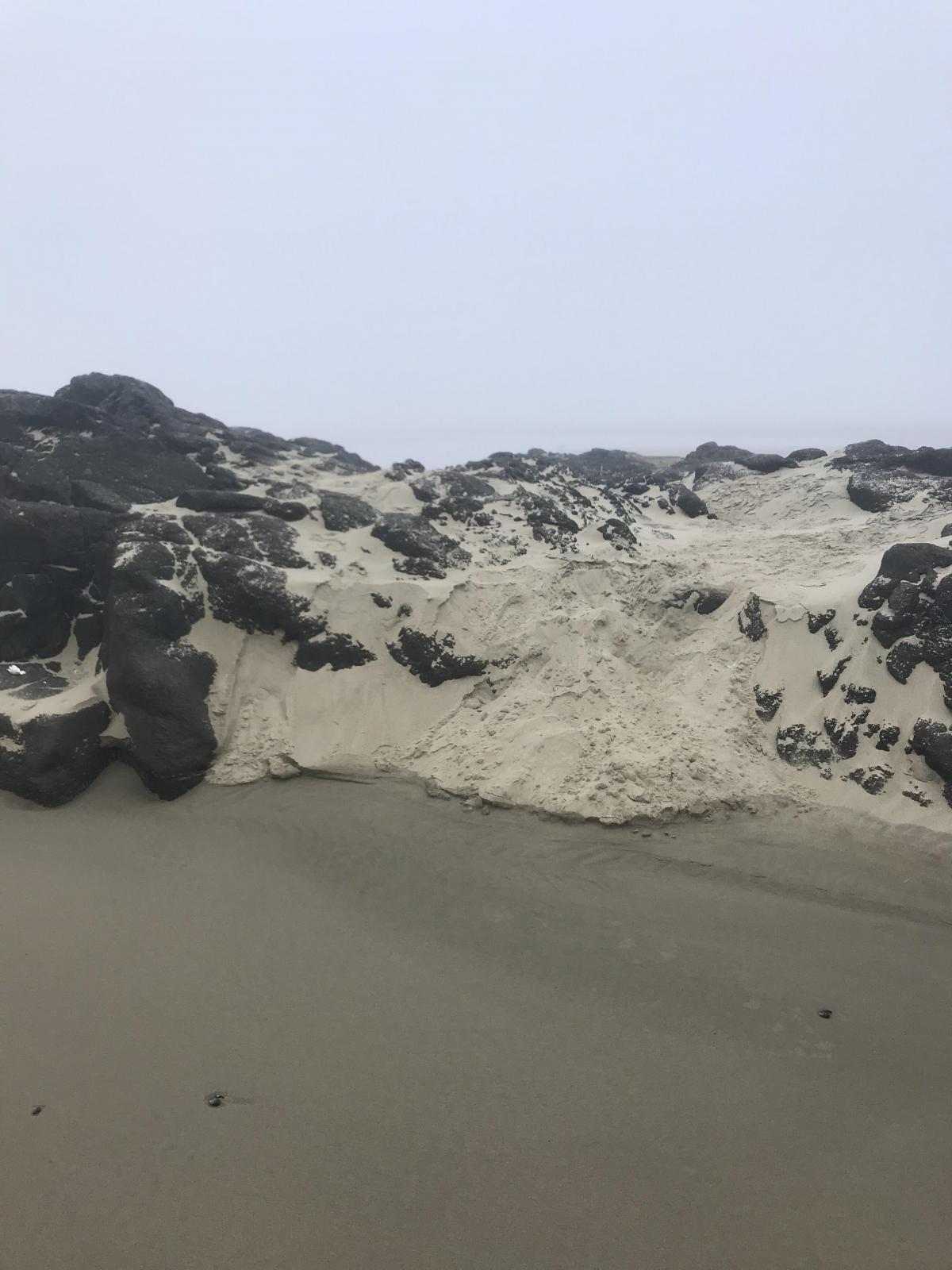 Rock formation almost completely obscured by sand