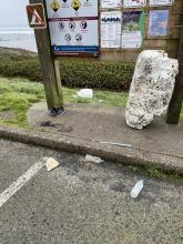 Styrofoam float, bottles and other trash in parking lot