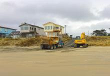 dump trucks on beach