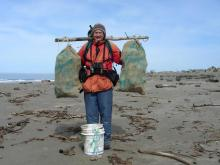 Dave Bilderback uses SOLV Gunny Bags, a beach-combed stick and beach-combed rope to haul plastic garbage from the mouth of New River and Two Mile Creek, Bandon, OR.