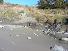 The telltale line of ragged sand indicates that the ocean has removed sand from the headland here.