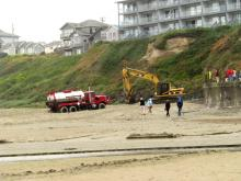 A large tracked excavator had to pull the tanker truck off the sand due to the poor traction.