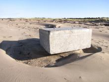 This large concrete pier washed inland about 200 yards by the large surf in the past weeks.  This is just balanced on a bit of sand, and could easily tip on a person.