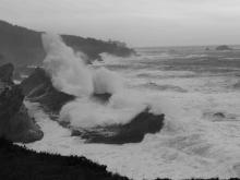 Large breakers hitting the coastline from low pressure storm system at sea.
