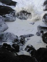 Large seas stir up foam along coastline.