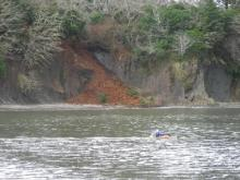 This picture shows a new landslide on the south side of Sunset Bay.  Also shown is a kayaker on the bay.