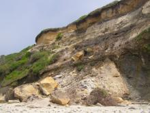 Sand and rock slides below the bluff where houses have been built near the bluff edge.