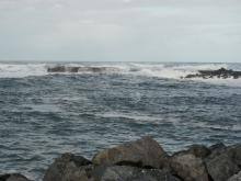 Waves engulf the north side of the jetty on the Coquille River mouth at high tide, 8.8 feet.