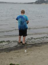 As I walked by I noticed he was fishing but not with a pole.Instead a stick stuck in the sand with a string attached?