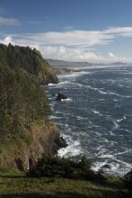 View south on mile 226 from location below illustrating rocky cliffed coastline, with the Lookout in middle distance (just north of south end of mile 226) with Devil's Punchbowl farther and Yaquina Head in greatest distance.