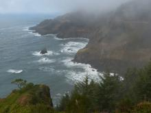 "North coastline of mile 226 on a slightly foggy, overcast day as viewed from the ""new"" viewing area in the interior of the Lookout at Otter Crest State Wayside"