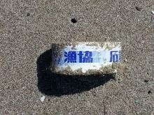 Roll of plastic tape with characters that could be Japanese or Chinese; found covered in dried seaweed