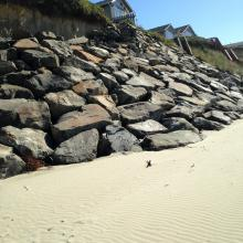 Apparently fill has been brought to build a gradual path from the bottom of rock stairs to beach.