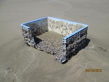 A blue open-top plastic storage bin with barnacles attached was washed ashore.  Dimensions are roughly 4'x6'x3'.  No identifying markings.
