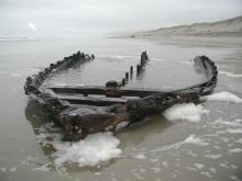 "Bow section of the Florence-based lumber schooner ""Bella"", blown ashore November, 1905.  Visible during winter low tides, at the Mile 168-169 boundary."