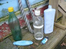 Blue plastic bottle with Asian writing, clear plastic bottle with Asian writing on cap and lower edge, lighter (Cuba), glass bottle with Asian writing, and small blue float with Asian writing.