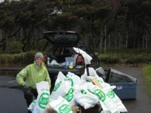 Surfrider volunteer and SOLV beach captain for Lost Creek, Serina Adams, poses next to the cleanup bags.