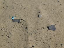 Closeup of roofing material dumped onto dunes