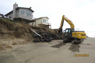 Machine continues to apply rock to bank of both properties