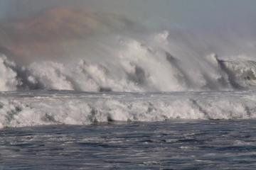 Wave spits out rainbows at roads end.