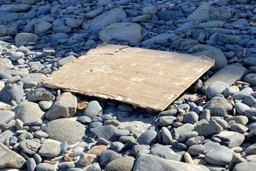 Sheet of plywood washed up by stairs
