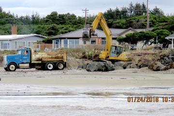 Truck dumps large boulders, supplying rock for rip-rap repair.