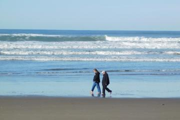 Couple walking at waters edge--note no attention to the surf
