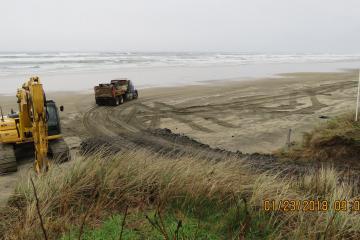 dump trucks on beach, large rock, rip-rap delivered