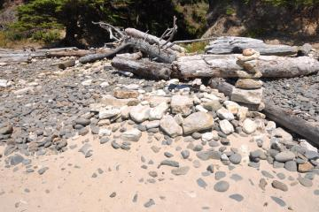 A 5-6 feet long burial mound of sand and rocks, with a cairn tombstone at the southern end of the mound on Short Sand Beach.