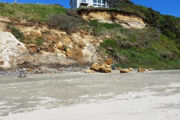 Boulders broken off from cliff face and fallen onto beach.