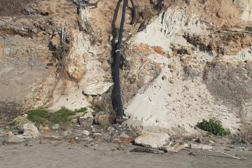 Continued erosion around a large drain pipe extending to beach.