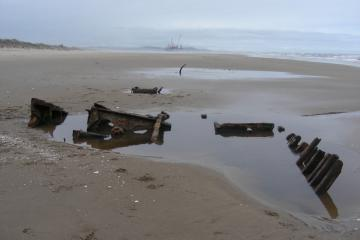 The removal of the New Carissa can be seen in the distance from the parts of this older shipwreck.