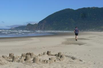 Running north towards  Neahkahnie Mountain, a runner passes a sand castle.