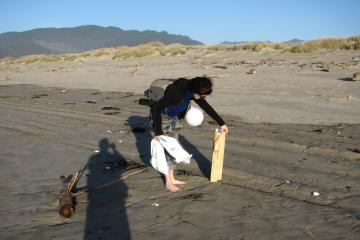 """My daughter Natanya picking up a large foam """"log"""".  Also note the SOLV bag, partially full, and the balloon, also found on the beach.  We also had another full SOLV bag with debris, mostly bottles, styrofoam, and rope/string of various kinds."""