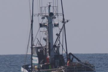 Crab boat Delma Ann tending a trap just outside the surf