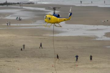 This helicopter was to lift the Lori Ann up as a tugboat pulled it off the beach.  Note the cable beneath the helicopter.  There was some problem and it had to land on the beach.