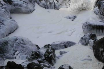 Large seas stir up foam along coastline.