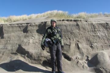 """Dave (6' 2"""") is standing next to the largest riptide embayment erosion on Mile 97."""